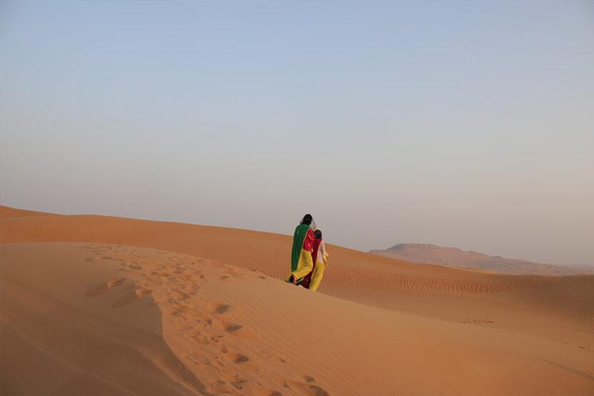 Zwei Personen laufen durch die Wüste von Dubai