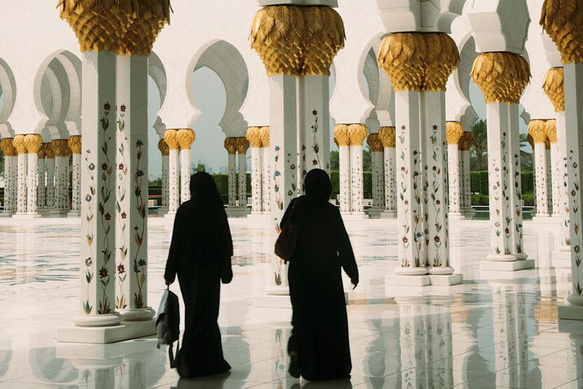 Zwei Personen laufen durch die Sheikh Zayed Moschee