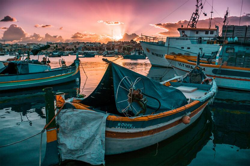 Sonnenuntergang und Dghajsa- einem typisch Maltesischen Boot